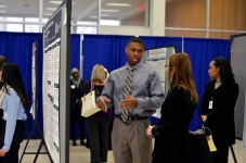 A research symposium participant explains his research