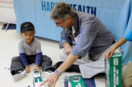 Dr. Marcus Hanfling plays with a young patient at Harris Health.