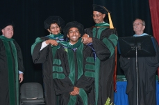 Proud parents hooding their graduate.