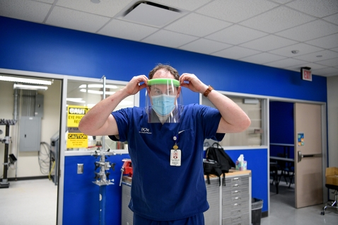 Jared Howell demonstrates a face shield made at Baylor.