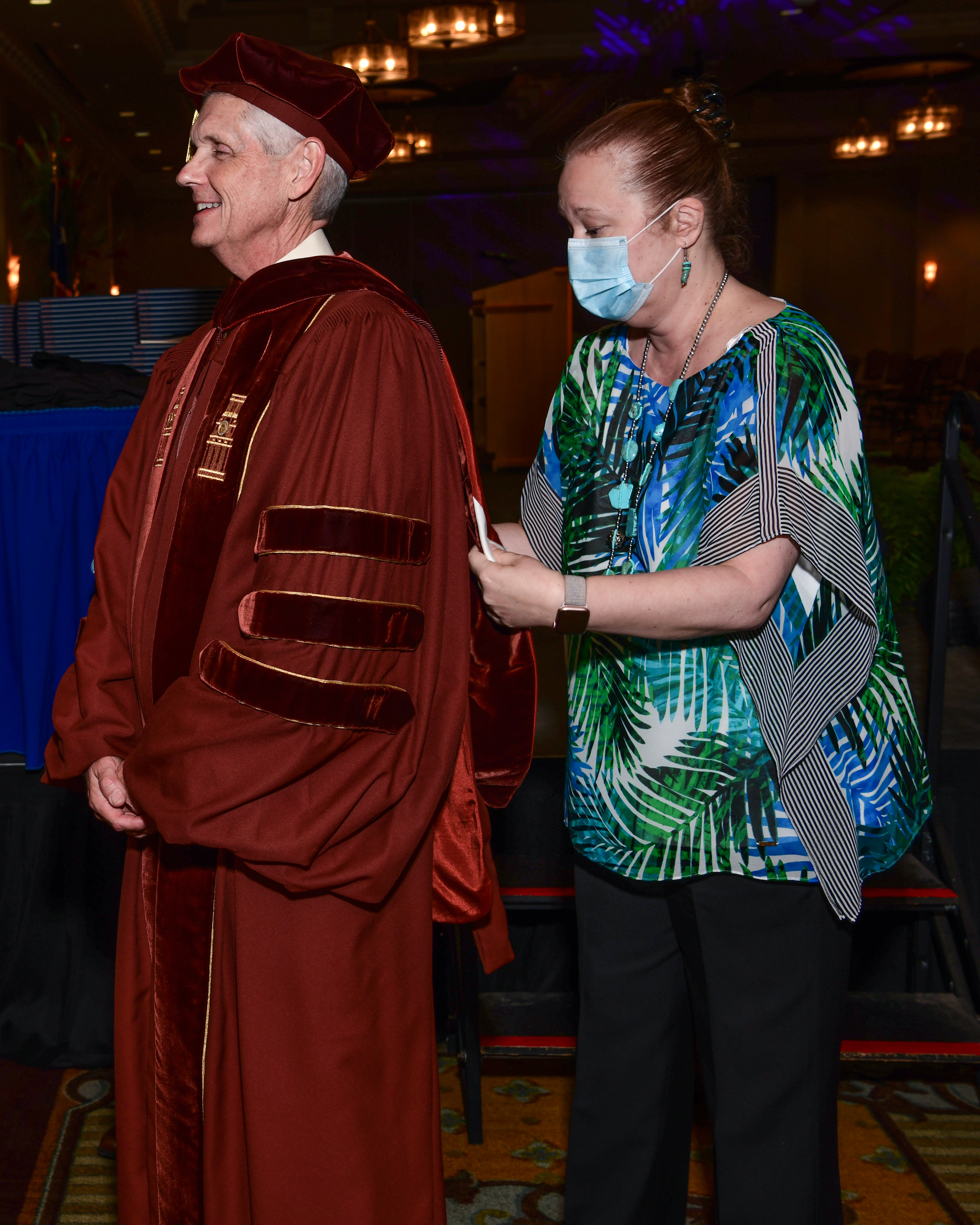 Jeannette Adams helps Dr. McLaughlin get ready for the graduation ceremony.
